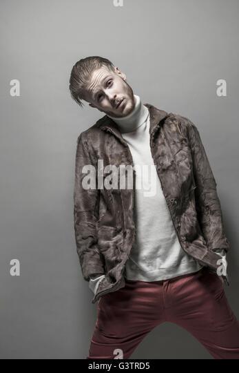 Studio portrait of a cool young man wearing a fur jacket. - Stock-Bilder