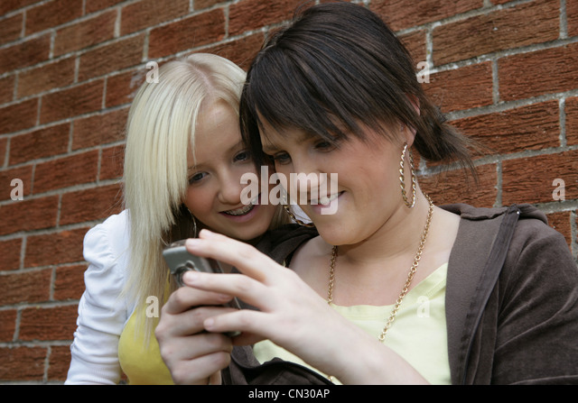 Two young women looking at mobile phone - Stock-Bilder