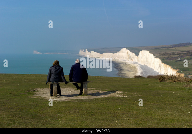Admiring the view from the hill above Birling Gap towards Sevens Sisters and Seaford Head on the Sussex coast, England - Stock Image