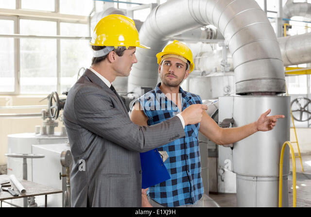 Worker with manager inspecting industrial area - Stock Image