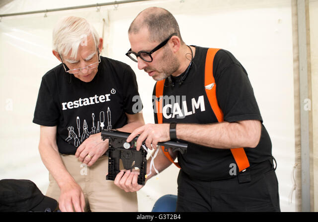 Restart project . A man wearing a t shirt saying 'calm' fixes a broken dvd player, watched by another engineer - Stock Image