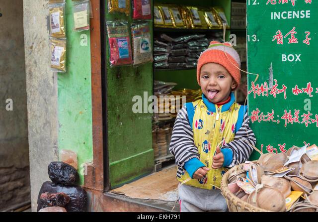 Nepali boy in front of an incense shop in Kathmandu - Stock Image