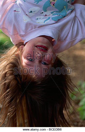 A young girl hanging upside down. - Stock Image