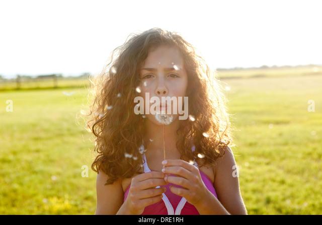 Girl wishing on a dandelion - Stock-Bilder