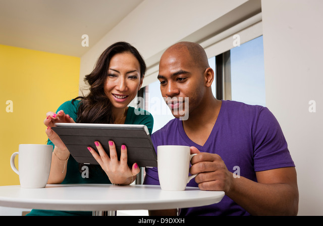 Mid adult couple looking at digital tablet and drinking coffee - Stock Image