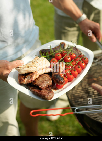 Close-up of person's hand holding sausages and cherry tomatoes on plate - Stock Image