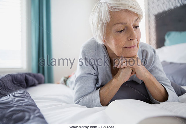 Woman reading book in bed - Stock Image