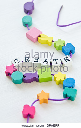 Colorful wooden toy beads in different shapes with letters that spell 'Create' strung together with cord - Stock Image