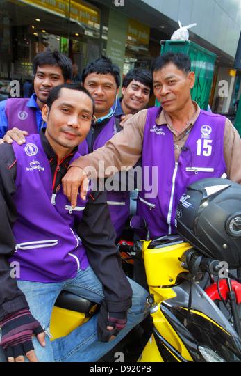 Bangkok Thailand Silom Silom Road Asian man motorcycle taxi drivers job coworkers - Stock Image