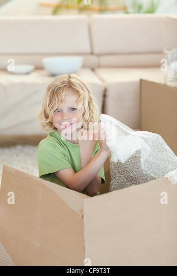 Boy playing with cardboard box - Stock Image