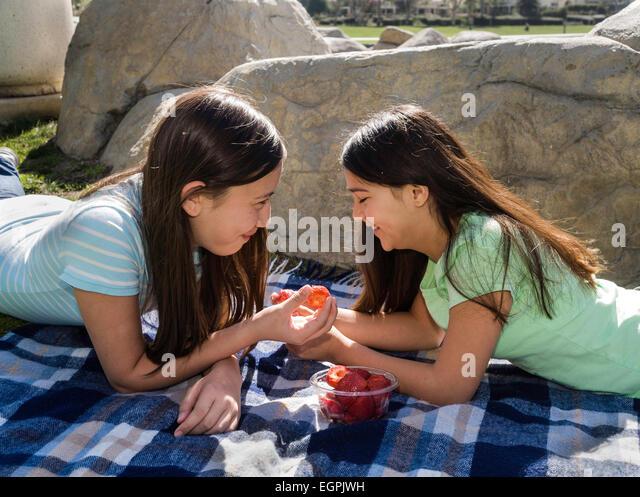 California Teens hanging out Teenage girls talking. Vietnamese/Caucasian and Hispanic/Caucasian girls share fruit. - Stock-Bilder