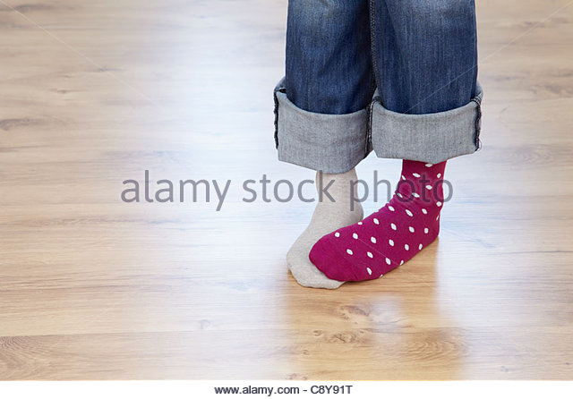 detail of woman wearing different socks - Stock Image