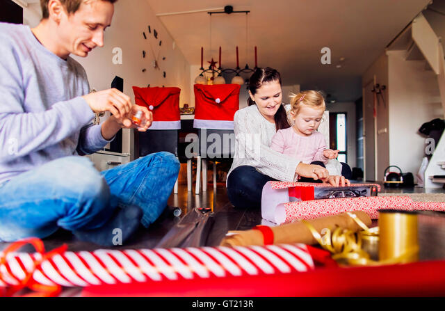 Happy mother and father with daughter wrapping Christmas presents at home - Stock-Bilder