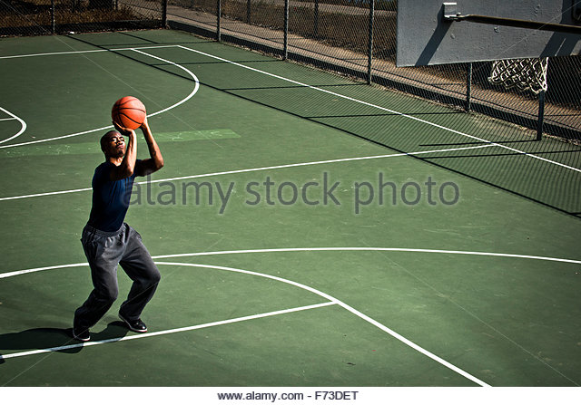 A basketball player practicing free throws. - Stock Image