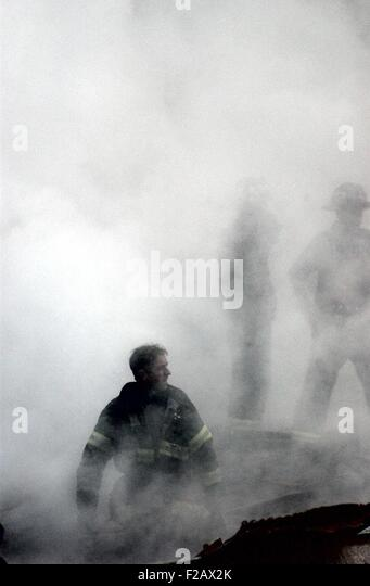 NYC Fireman emerges from the smoke and debris of the World Trade Center on Sept. 14, 2001. New York City, after - Stock-Bilder