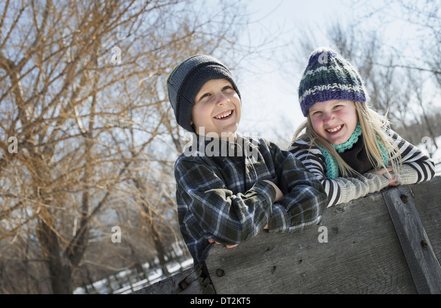 Winter scenery with snow on the ground Two children in knitted hats leaning on a fence - Stock Image