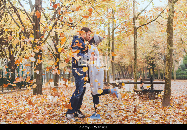 autumn kiss, young loving couple in the park with falling leaves - Stock Image