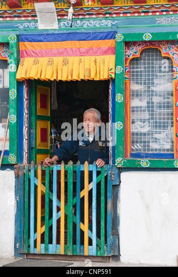 Asia, Bhutan, Bumthang. Man in shop doorway - Stock Image