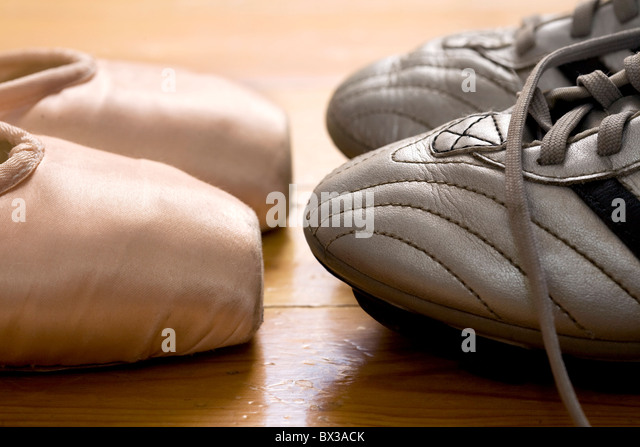 still life of ballet shoes and football boots - Stock Image