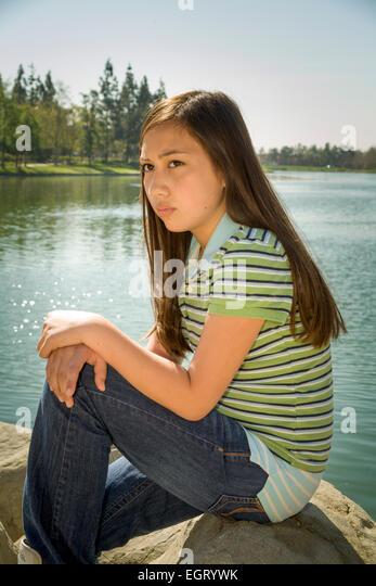 Vietnamese/Caucasian girl sits outside meditating 11-13 years old .MR  © Myrleen PearsonVietnamese/Caucasian - Stock-Bilder