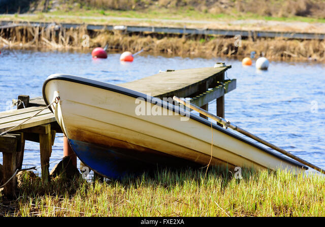 Small open rowboat pull up from the river beside a wooden pier. - Stock Image