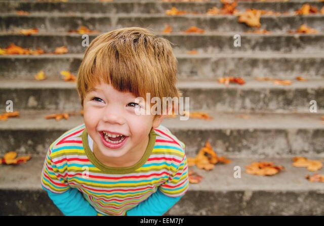 Boy (2-3) laughing while standing on steps - Stock Image