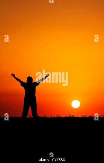 A young person with hands in air in front of beautiful blood red sunset - Stock Image