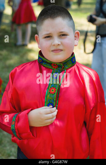 the boy's portrait in a red national Russian shirt - Stock-Bilder