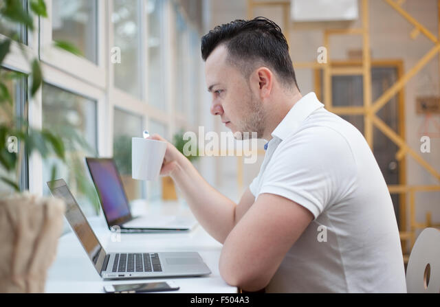 Man using laptop in white office - Stock Image