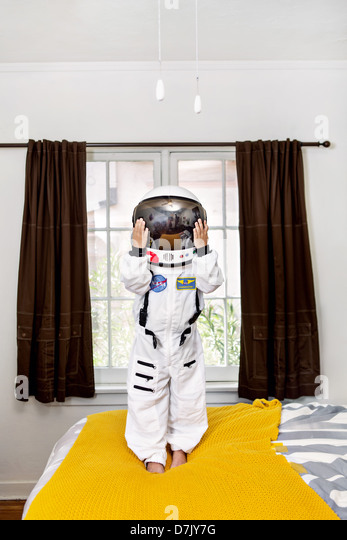 portrait of boy standing on his bed in space suit - Stock Image