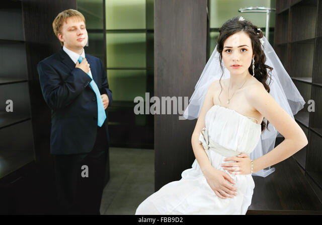 Newlyweds on background of office furniture empty cabinets, relationship between man and woman. Beautiful bride - Stock Image