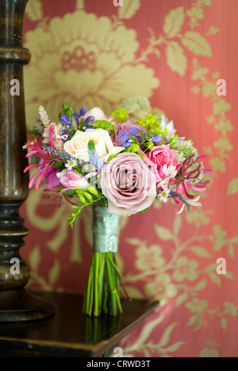 wedding bouquet on a wooden shelf with vintage patterned wallpaper - Stock Image