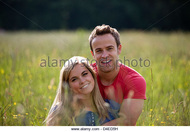 A young couple sitting in long grass embracing - Stock Image