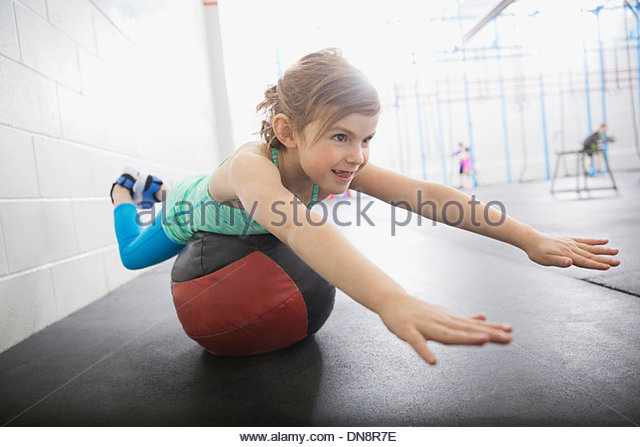 Girl balancing on medicine ball - Stock Image