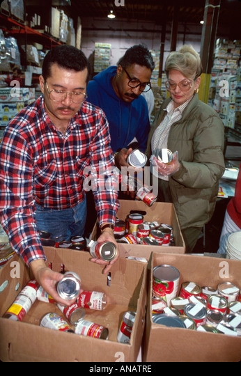 New Jersey Hoboken Food Bank volunteers sort donations Black male community service - Stock Image