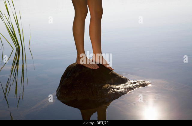 Woman standing on rock - Stock Image