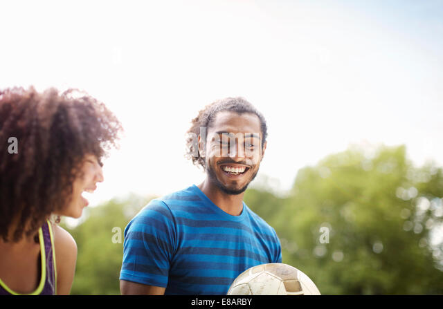 Young soccer couple chatting and laughing together in park - Stock Image