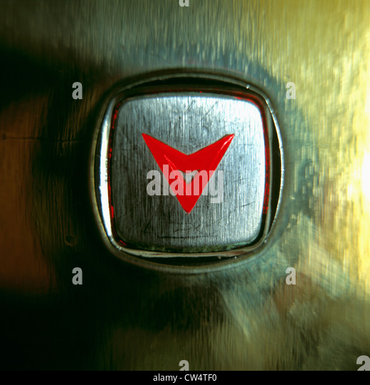 Close-up of an elevator button with a glowing red arrow pointing down - Stock Image