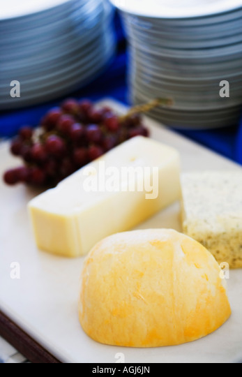 Close-up of slices of cheese with red grapes on a cutting board - Stock-Bilder
