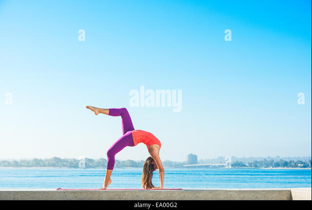 Young woman practicing yoga position at Pacific beach, San Diego, California, USA - Stock-Bilder