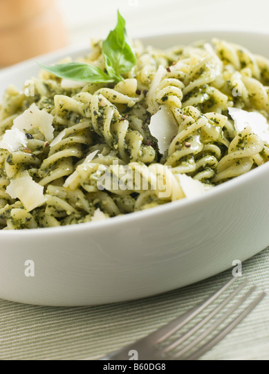 Bowl of Fusilli Pasta dressed in Pesto with Parmesan Shaves - Stock Image