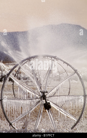 Irrigation apparatus shows the sign of a cold night as it is covered with ice early in the morning in the Idaho - Stock Image