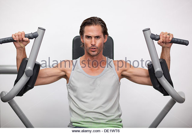 Portrait of man using exercise equipment in gymnasium - Stock Image
