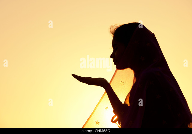 Indian girl holding out her hand wearing a star veil at sunset. Silhouette. India - Stock Image