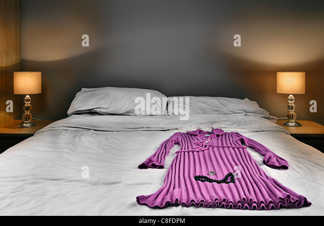 Ladies Pink Dress and Jewelery On Bed - Stock Image