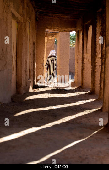Traditional dressed man walks through an arch way. - Stock Image