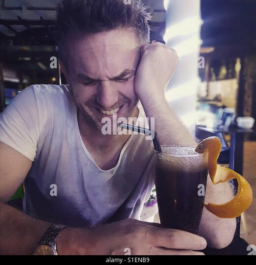 Man laughing whilst drinking a cocktail - Stock Image