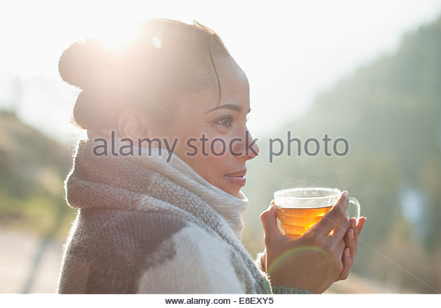 Close up of smiling woman drinking tea outdoors - Stock-Bilder