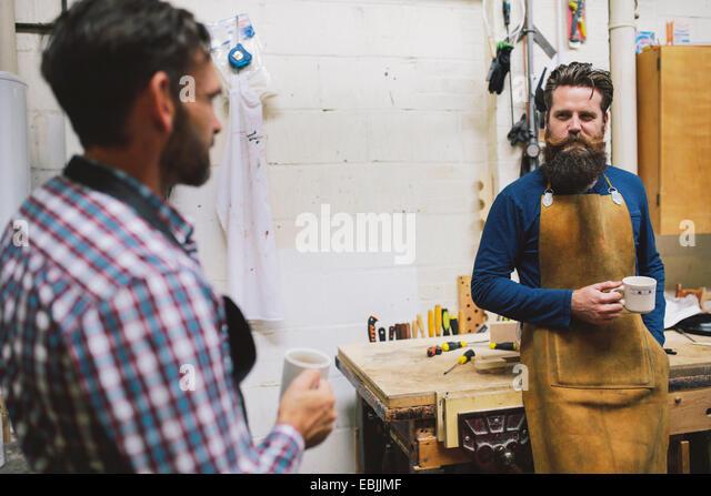 Two craftsmen chatting in pipe organ workshop - Stock Image