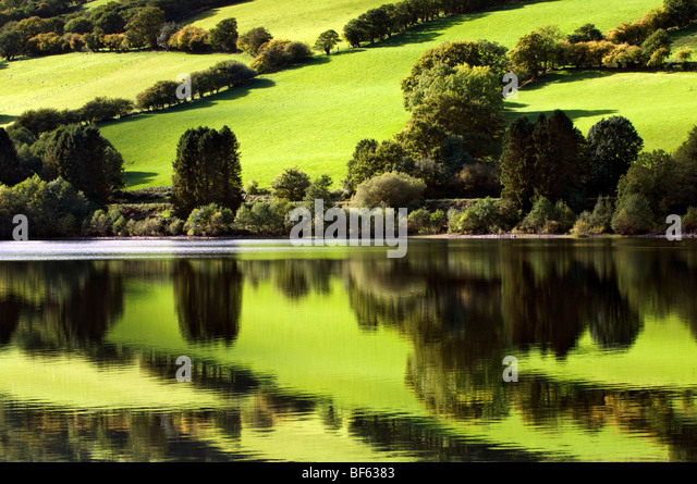 Perfect reflection of green fields at Talybont reservoir, Brecon Beacons in Wales taken on beautiful bright sunny - Stock-Bilder